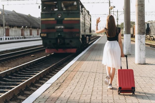 Viajante morena feminina com mala vermelha andando na estação raiway