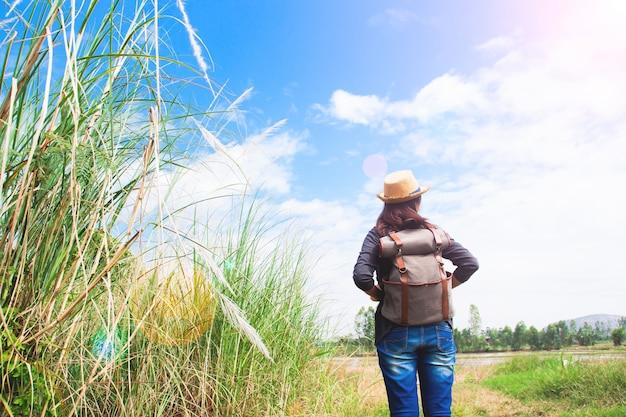Viajante mulher feliz olhando para o céu azul com campo de gramíneas, conceito de viagem wanderlust, espaço para texto