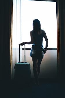Viajante mulher levar uma bagagem e check-in no hotel.