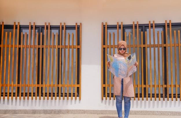 Viajante mulher muçulmana asiática olhar e segure no mapa de mãos, as pessoas planejando viagem