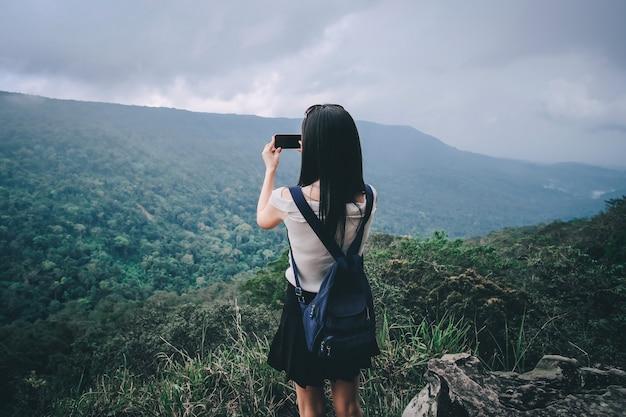 Viajante mulher tendo foto vista da natureza no topo da montanha durante as férias.