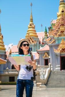 Viajante mulher usando mapa local e encontrar o caminho para ir ao destino.