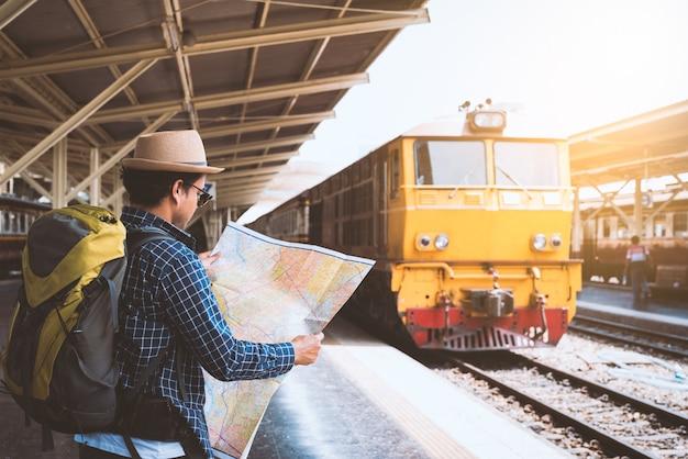 Viajante na estação de trem, olhando o mapa