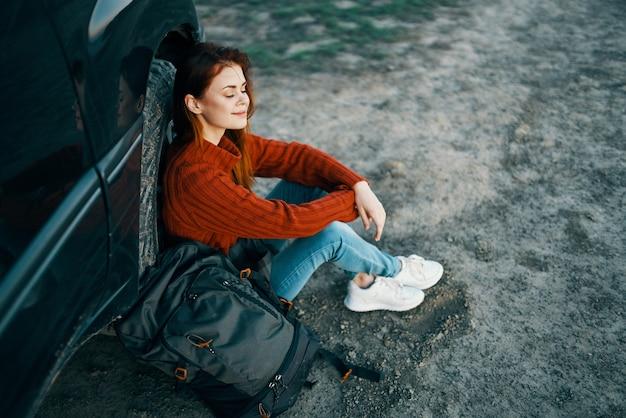 Viajante nas montanhas perto do carro, descansando na natureza com uma mochila vista de cima