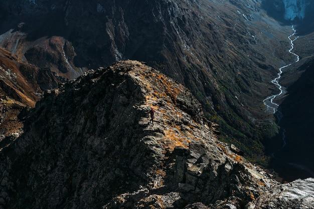 Viajante nas montanhas. um homem corre ao longo de uma cordilheira em dombay. homem ao nascer do sol nas montanhas. um homem está viajando no cáucaso. caminhante ao pôr do sol nas montanhas. viagem ao cáucaso