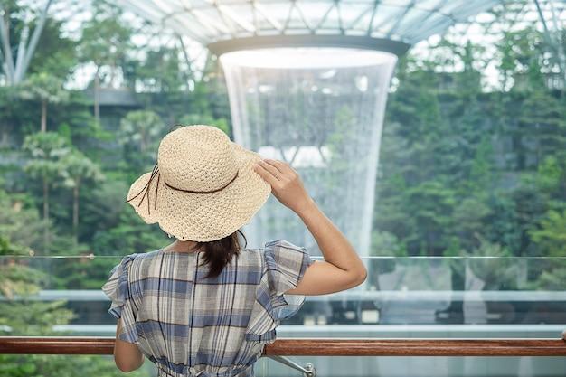 Viajante olhando para o vórtice de chuva linda no aeroporto de jewel changi