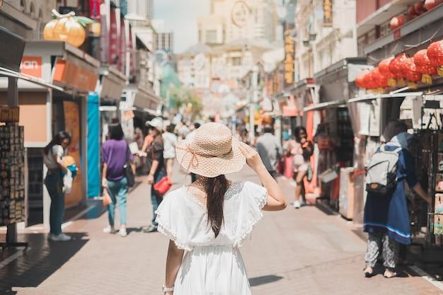 Viajante que anda no mercado de rua de chinatown em singapura.