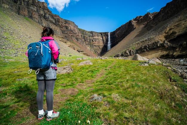 Viajante que caminha na cachoeira de hengifoss, islândia.