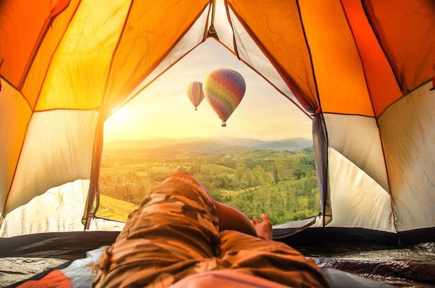 Viajante que olha o balão de ar quente e a névoa bonitos no nascer do sol.
