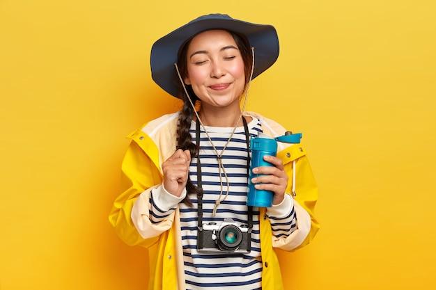 Viajante satisfeita com aparência asiática, usa chapéu, macacão listrado e capa de chuva, câmera retro no pescoço, segura o frasco de bebida quente, isolado sobre a parede amarela