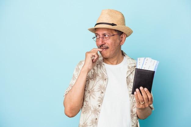Viajante sênior indiano de meia idade, segurando o passaporte isolado no fundo azul, relaxado pensando em algo olhando para um espaço de cópia.
