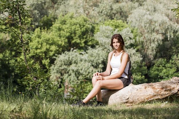 Viajante sentado em um tronco de árvore
