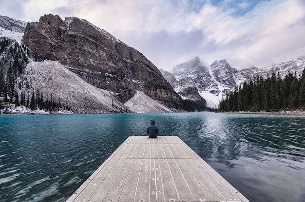 Viajante sentado no cais de madeira com montanha rochosa no lago moraine no parque nacional de banff