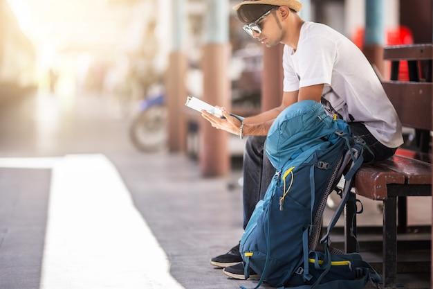 Viajante, sentado sozinho na cadeira de madeira no estação de trem.