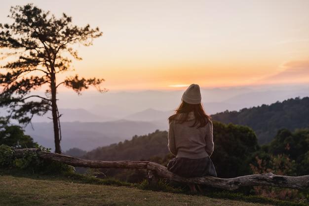 Viajante solitário jovem olhando o pôr do sol e belas vistas sobre a montanha
