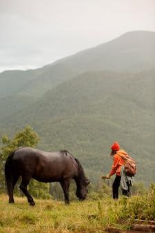 Viajante tentando alimentar um cavalo