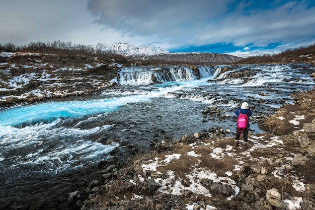 Viajante tirando foto da cachoeira de bruarfoss na temporada de inverno