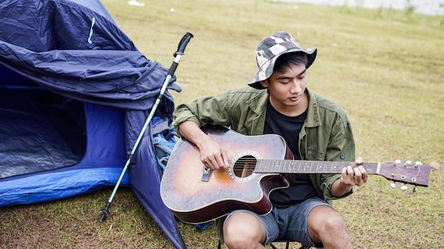 Viajante tocando violão no acampamento