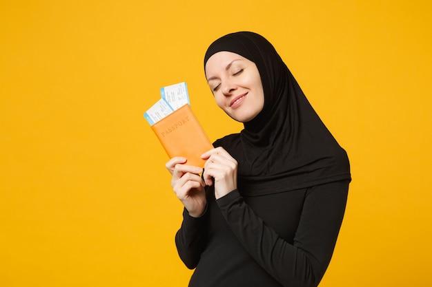 Viajante turista jovem árabe muçulmana em roupas pretas de hijab segurar ingressos para passaporte isolados no retrato de parede amarela. conceito de estilo de vida religioso de pessoas.