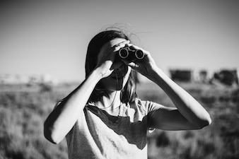 Viajante usando binóculos para avistar um pássaro