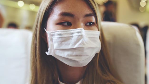 Viajante usando máscara facial enquanto viaja em um avião comercial