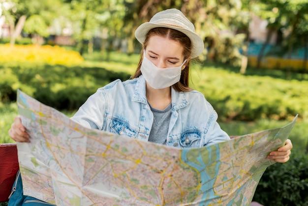 Viajante usando máscara médica, olhando para o mapa