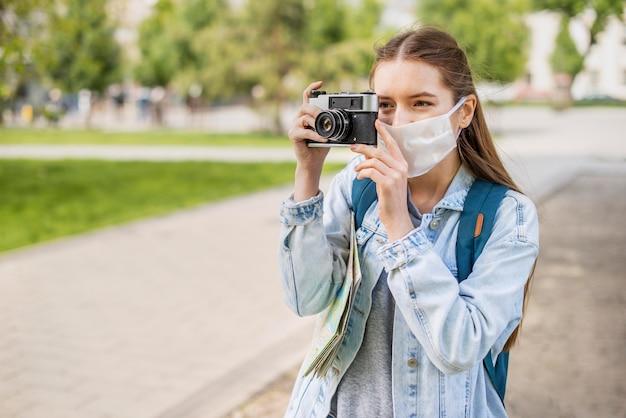 Viajante usando máscara médica tirando uma foto