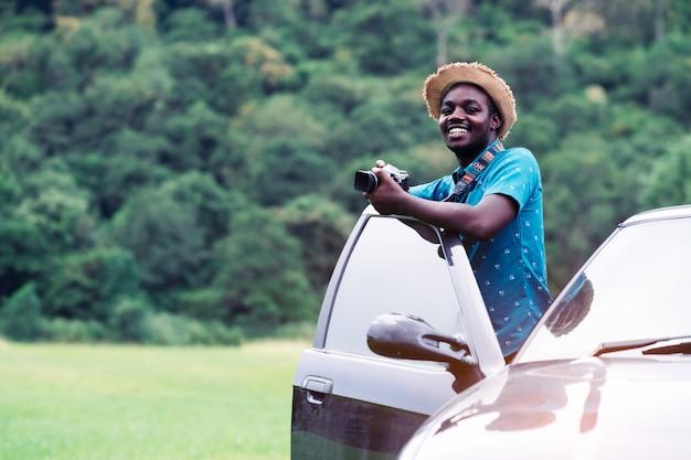 Viajantes africanos em pé e segurando a câmera com o carro