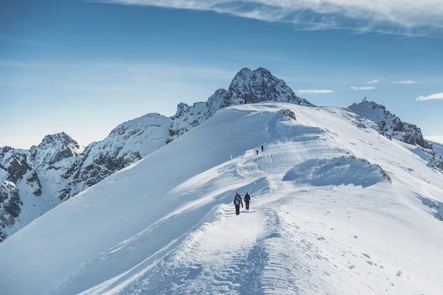 Viajantes alpinista vai ao pico nevado em montanhas.