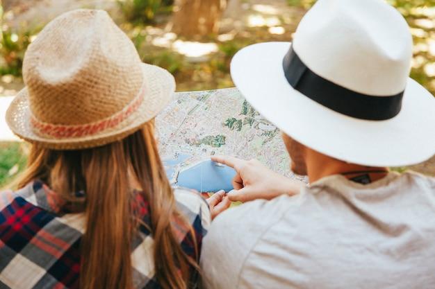 Viajantes apontando o mapa no parque