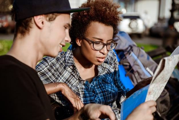 Viajantes assistindo rota no mapa, sentado no banco do parque.