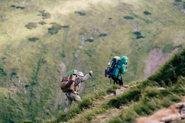 Viajantes com mochilas e equipamentos turísticos profissionais escalando montanhas. atingindo o topo. caminhada alpina. viagem de férias.