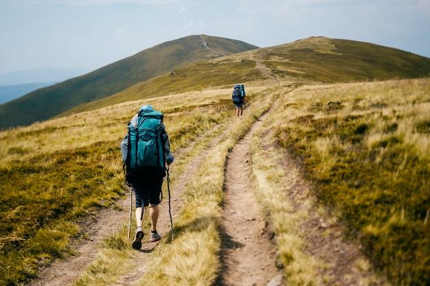 Viajantes com mochilas pesadas andam nas montanhas