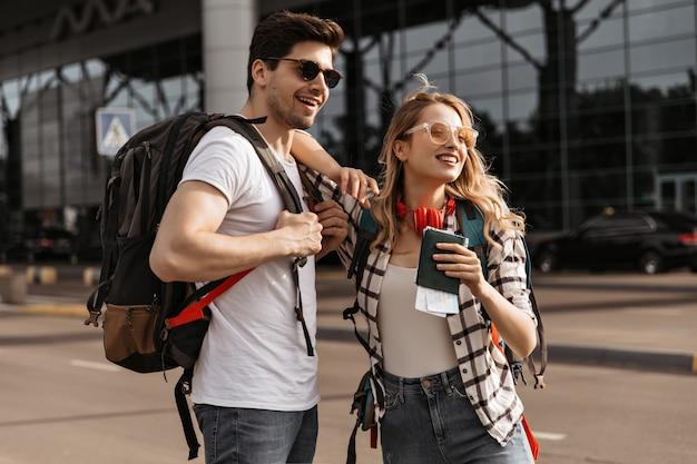 Viajantes com mochilas posam perto de um aeroporto moderno