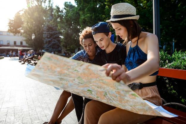Viajantes de amigos sorrindo, olhando a rota no mapa, sentado no banco.