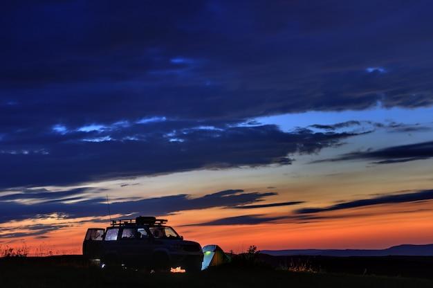 Viajantes de carro ao pôr do sol nas montanhas no norte do cáucaso, na rússia.