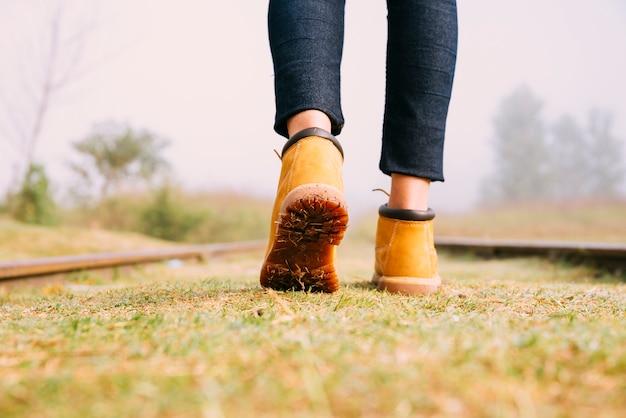 Viajantes de garota close-up botas andando na estrada de ferro