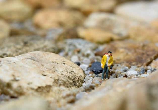 Viajantes de mochila em miniatura caminhando na rocha, conceito de viagem