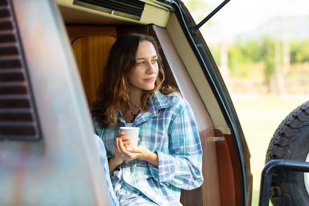 Viajantes de mulher bonita caucasiana feliz desfrutam de café de manhã na natureza, férias em carro de acampamento
