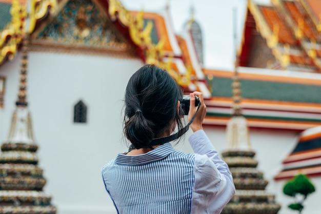 Viajantes de solo de mulher asiática e tirar foto antigos edifícios de pagode