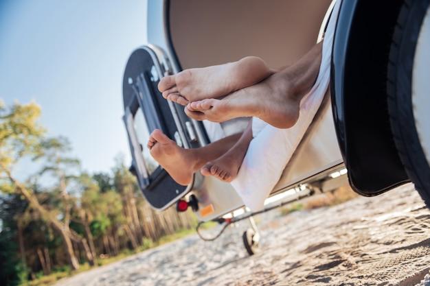 Viajantes descalços. casal adorável de viajantes descalços, deitado em seu trailer compacto perto da praia