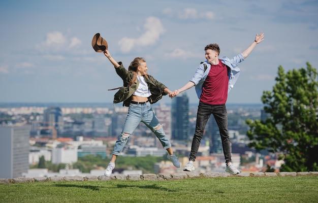 Viajantes do casal jovem alegre na cidade de férias, pulando. paisagem urbana em segundo plano.