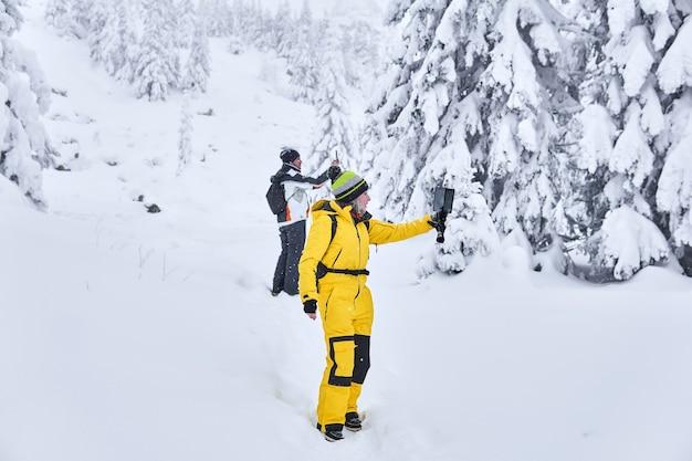 Viajantes em uma floresta de montanha no inverno tiram uma selfie tendo como pano de fundo uma paisagem de neve
