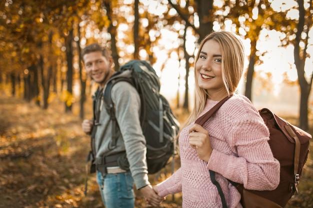 Viajantes felizes andando por um caminho de floresta de outono ao ar livre