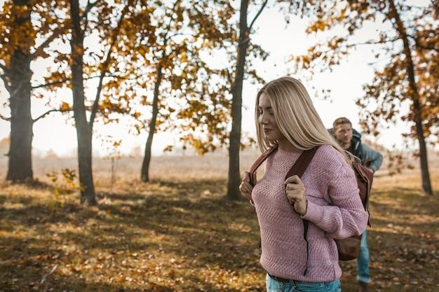 Viajantes felizes com mochilas começa sua jornada no outono floresta ensolarada