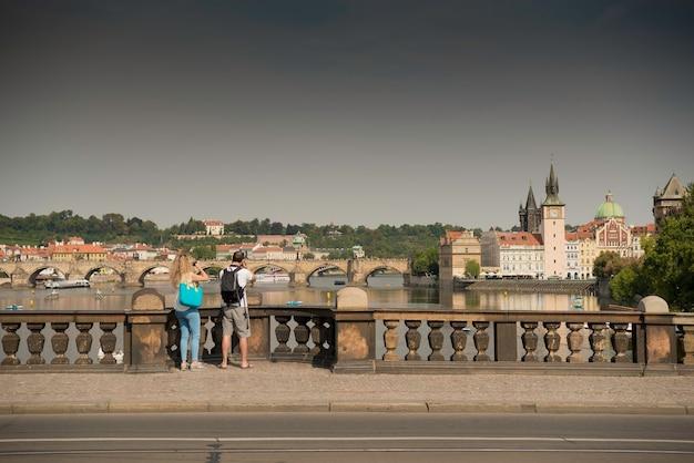 Viajantes indefinidos com mochilas tirando fotos de praga na ponte da legião, república tcheca
