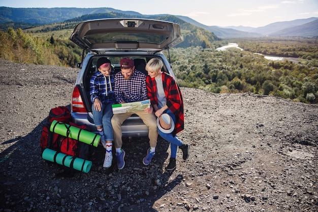 Viajantes jovens amigos sentado no porta-malas do carro e olhando para o mapa de papel.