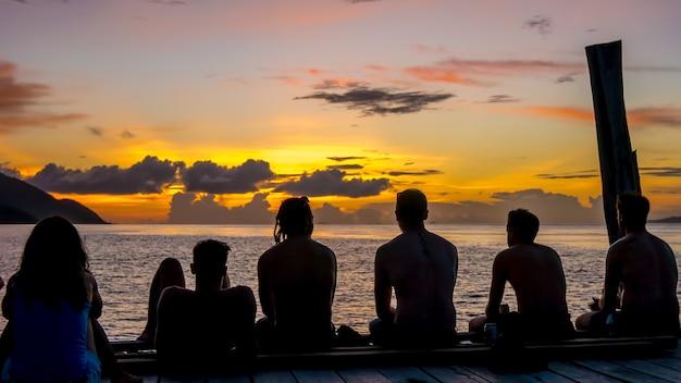 Viajantes, mergulhadores relaxando no cais em sunset, ilha de kri. raja ampat, indonésia, papua ocidental.