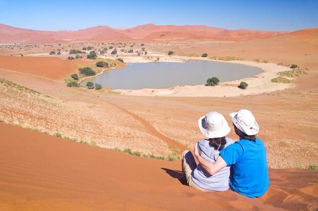 Viajantes na áfrica, casal em férias românticas na namíbia, olhando a bela paisagem do deserto do namibe