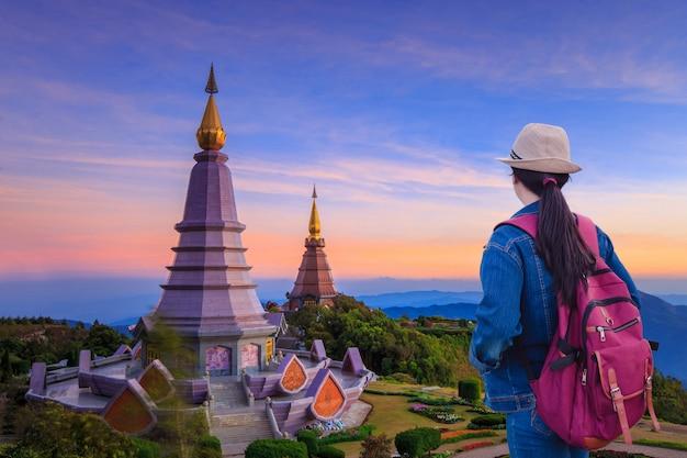 Viajantes que olham a paisagem de dois grandes pagodes no topo da montanha de doi inthanon, chiang mai, tailândia.